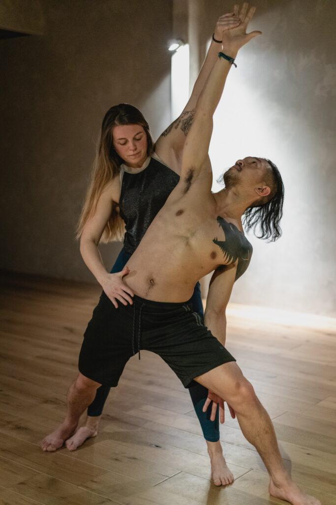 Yoga teacher assisting yoga student.